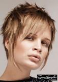 Asymetricky střižený krtký účes stylizovaný do rozcuchu, hnědé barvy s blond melírem a ofinou na straně
