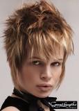 Lehce extravagntní účes z krátkých sestříhaných vlasů hnědé barvy s blond melírem a ofinou do čela