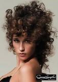 Polodlouhý částečně vyčesaný účes z kudrnatých vlasů hnědé barvy