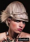 Umělecky vytvořený společenský účes z dlouhých rovných vlasů blond barvy, s copánky