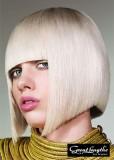 Geometricky střižené mikádo z polodlouhých rovných vlasů s rovnou ofinou do čela, blond platinové barvy