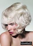 Zvlněné mikádo z krátkých vlasů blond barvy s ofinou do čela