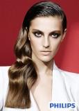 Účes z dlouhých uhlazených vlasů ležících na rameni, hnědé barvy, mírně zvlněný