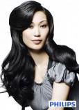 Elegantní jemně zvlněný účes z dlouhých vlasů černé barvy s pěšinkou na straně