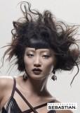 Vyčesaný, divoce stylizovaný účes z dlouhých mírně zvlněných vlasů hnědé barvy, s asymetricky sttřiženou ofinou