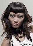 Extravagantně střižený účes z dlouhých vlasů hnědé barvy,s asymetricky střiženou ofinou do čela