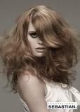 Přirozeně zvlněný účes z dlouhých hustých vlasů hnědé barvy