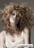 Kudrnatý účes z dlouhých vlasů měděné barvy s blond melírem