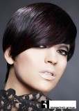 Asymetricky střižený krátký účes z rovných vlasů tmavofialové barvy, s ofinou na patku