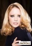 Polodlouhý účes z mírně zvlněných vlasů blond barvy s pěšinkou na straně